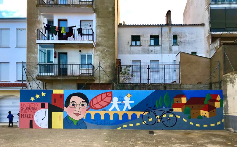 mural izas azulpatio dibujando la palabra ceip diego lainez frente