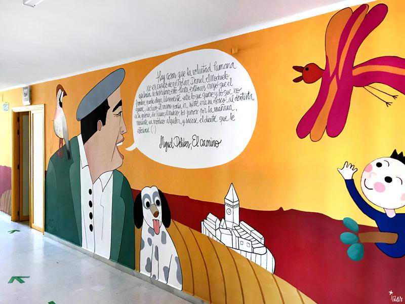 mural izas azulpatio dibujando la palabra madrigal derecha